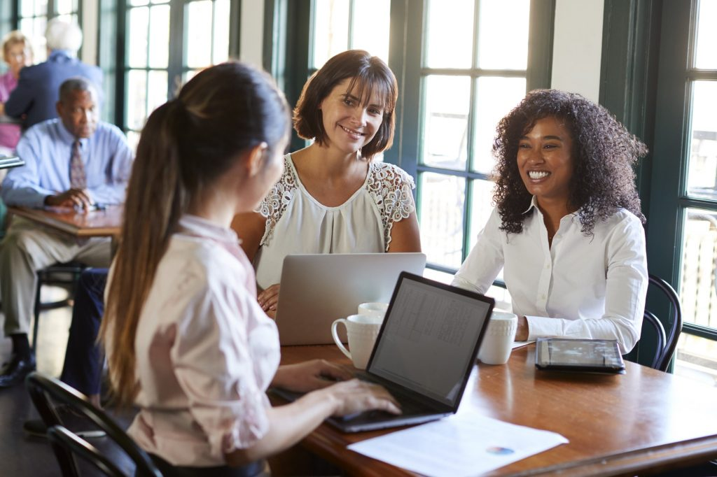 Businesswomen Having Informal Meeting Around Table In Coffee Shop
