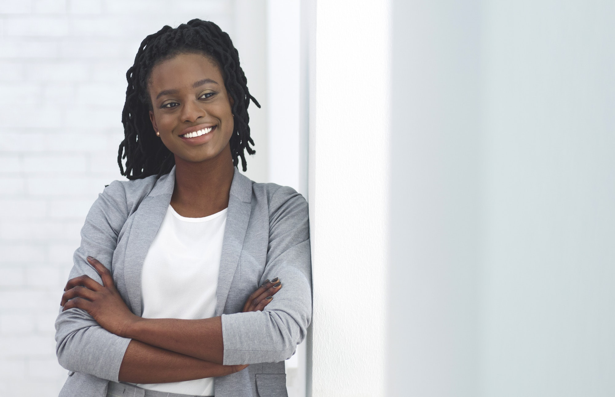 African American Business Girl Smiling At Camera Crossing Hands Indoor