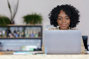 Black woman freelancer working with laptop at cafe