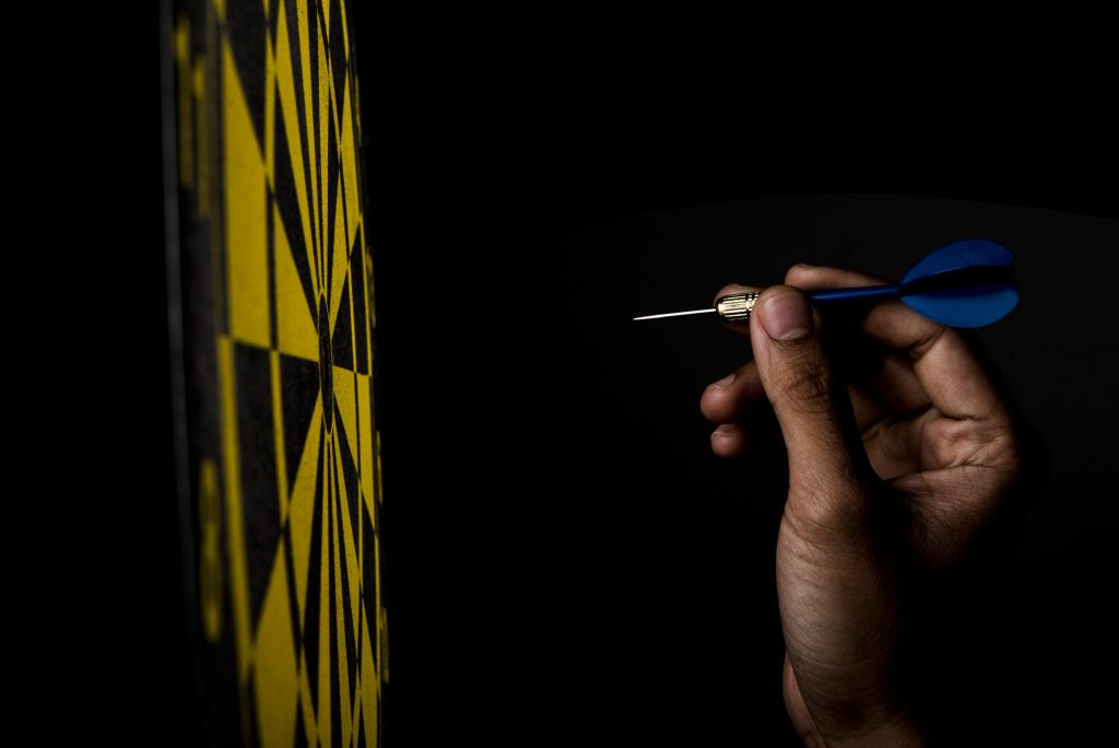 dartboard with arrow on black background, success concept