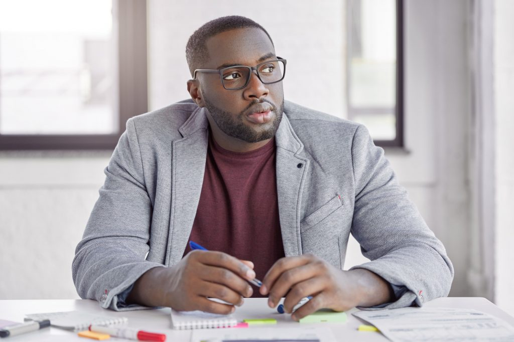 Experienced dark skinned thoughtful male economist writes notes for delegate project, works at offic
