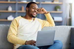 happy african american guy enjoying weekend at home, using laptop