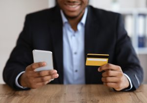 Black man in suit with mobile phone and credit card