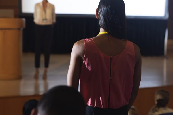 Rear view of mixed race woman from the audience standing and asking query in the auditorium